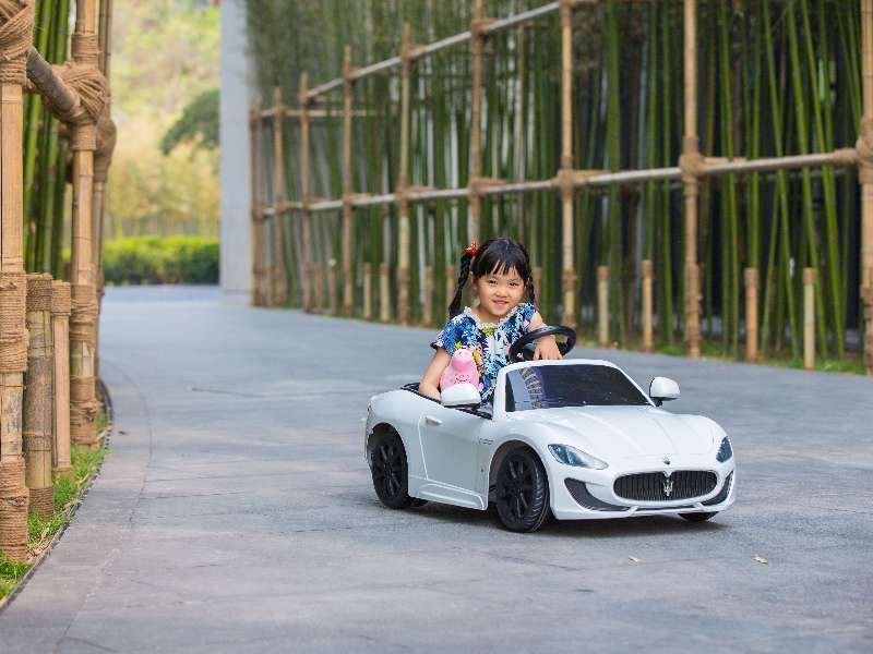 A yung girl in a Maserati toy