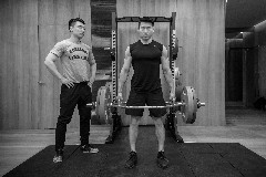 An instructor and a weight lifter at the Workshop Gymnasium of The Bvlgari Hotel Shanghai